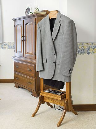 The Suit Valet with power strip is shown in oak The Amish Home