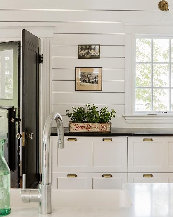 Black and white cottage kitchen features a white shaker
