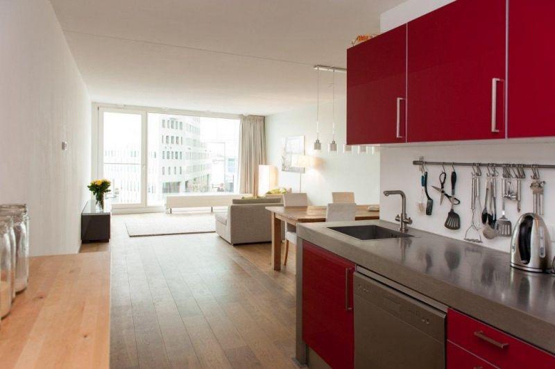 Open space, red kitchen. (Westerdoksdijk 1013 AD Amsterdam | Expat Housing)