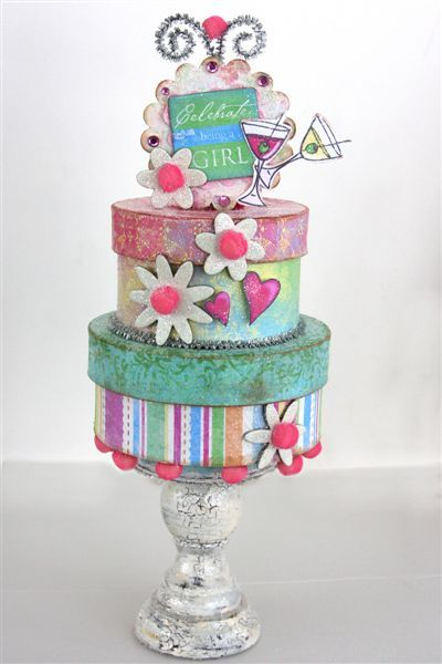 papermache boxes all decked out with scrapbook paper on a candlestick