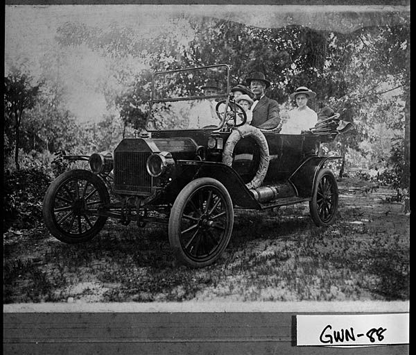 Photograph Of A Family Riding A Car On A Dirt Road