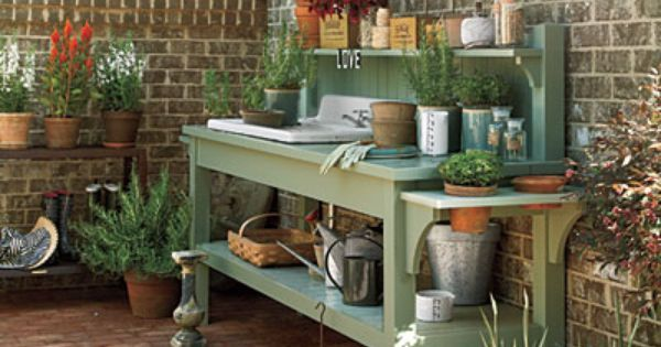 cedar potting table with dry sink and supplies on a deck with stone wall  behind