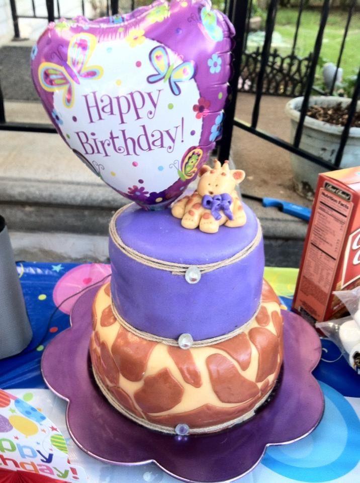 Purple birthday cake with fondant giraffe and giraffe print.