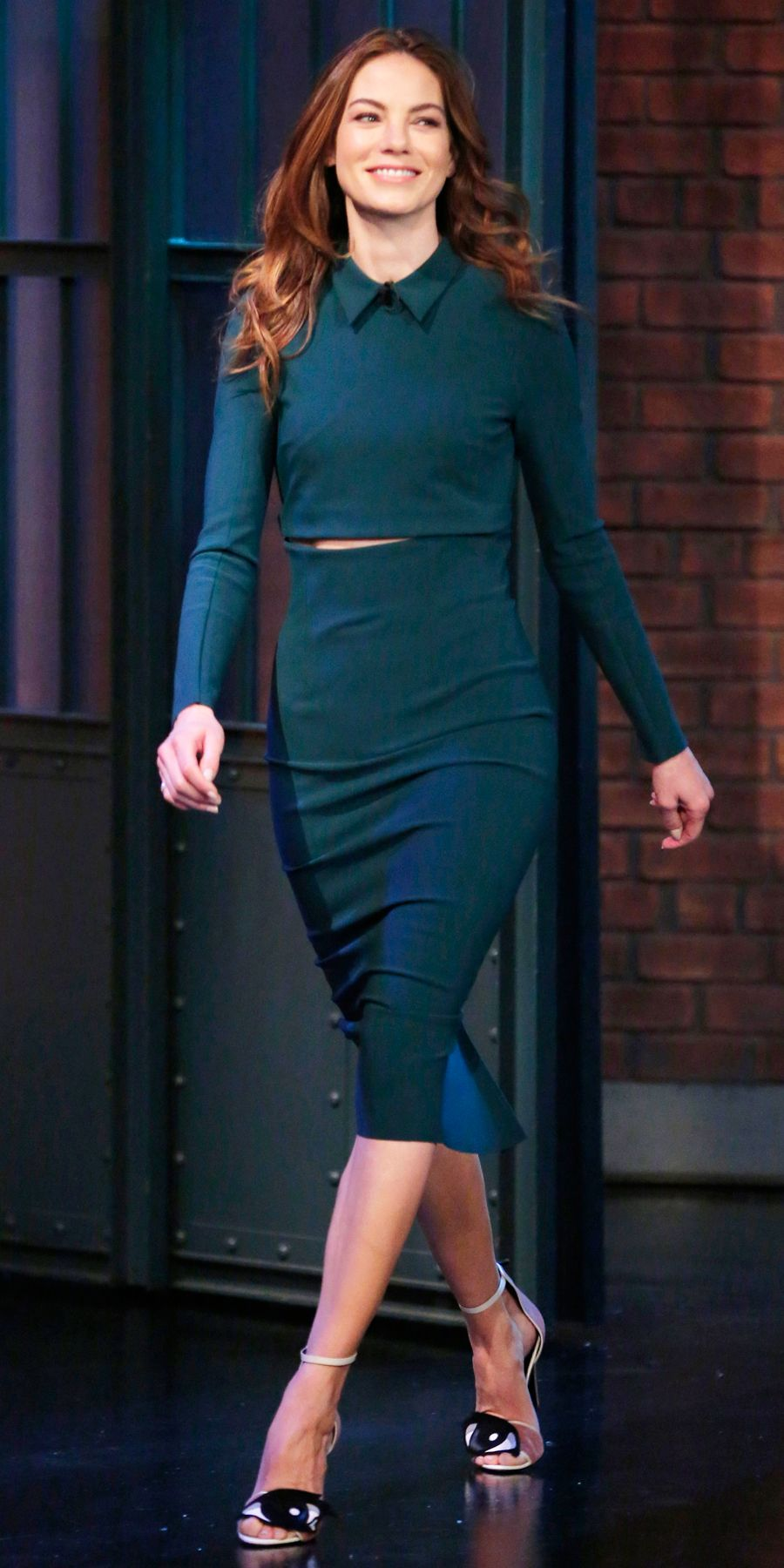 Michelle Monaghan bared just a sliver of midriff for an appearance on the set of Late Night with Seth Meyers in a teal cropped collared top and a high-waist pencil skirt, a streamlined set by Greta Constantine, and playful Pierre Hardy sandals.