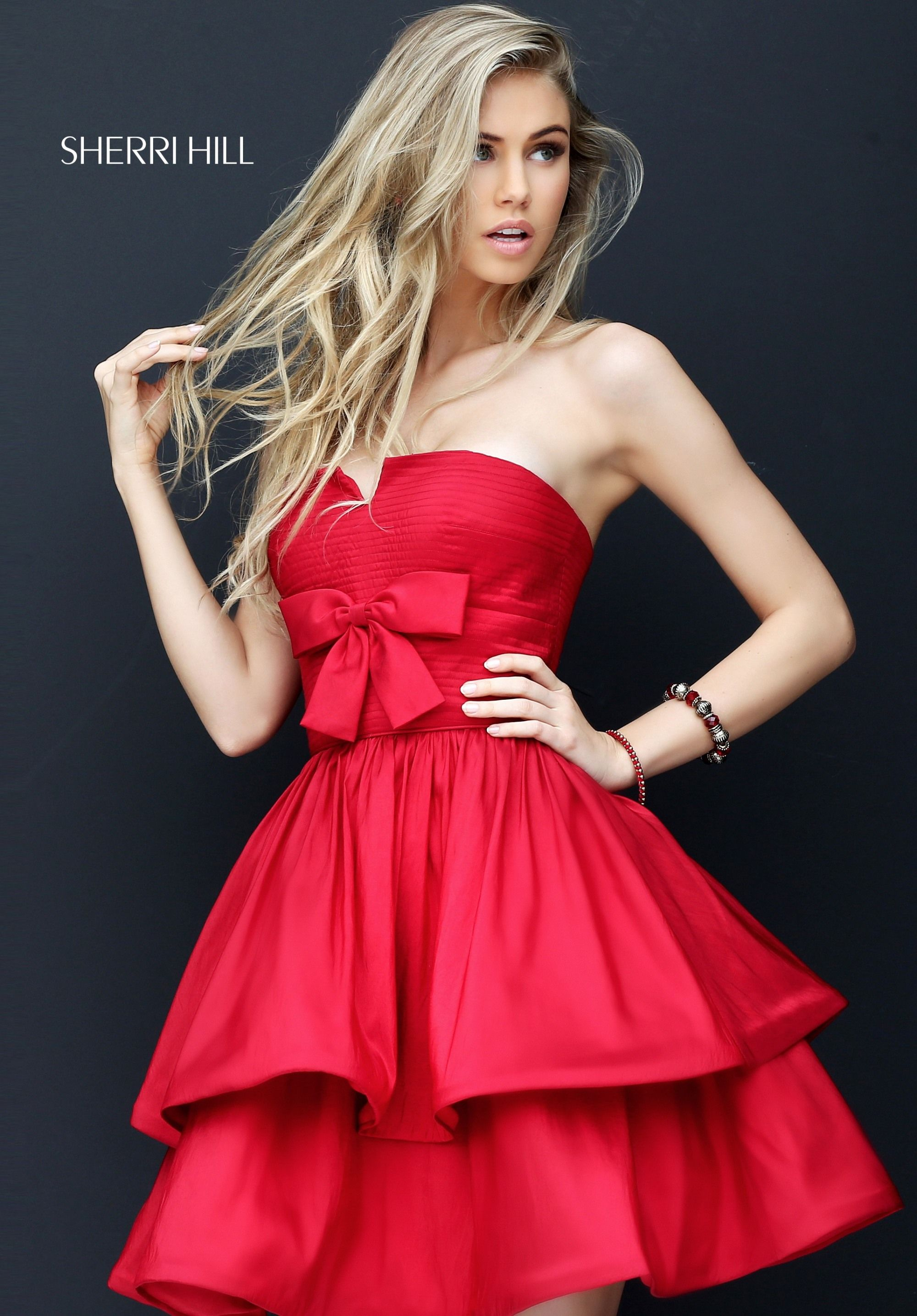 Sherri Hill 50546 is a strapless short party dress with a two-tiered full  skirt and a bow on the bodice.