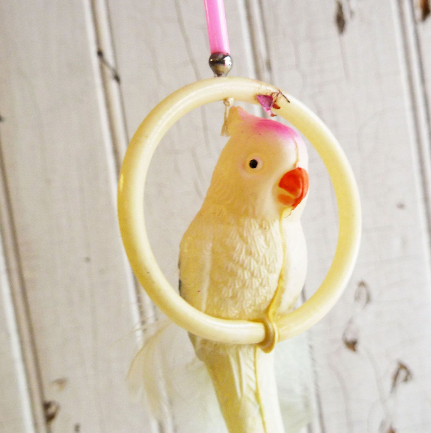 Vintage celluloid cockatoo birdcage toy with feather tail mid