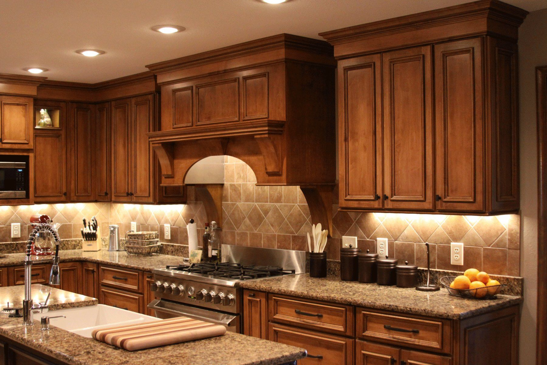 Shiloh S Acorn Maple Cabinetry With Black Glaze Creates A Warm And Inviting Kitchen Recessed Under Cabinet Lights Illuminate The Room Improve Function