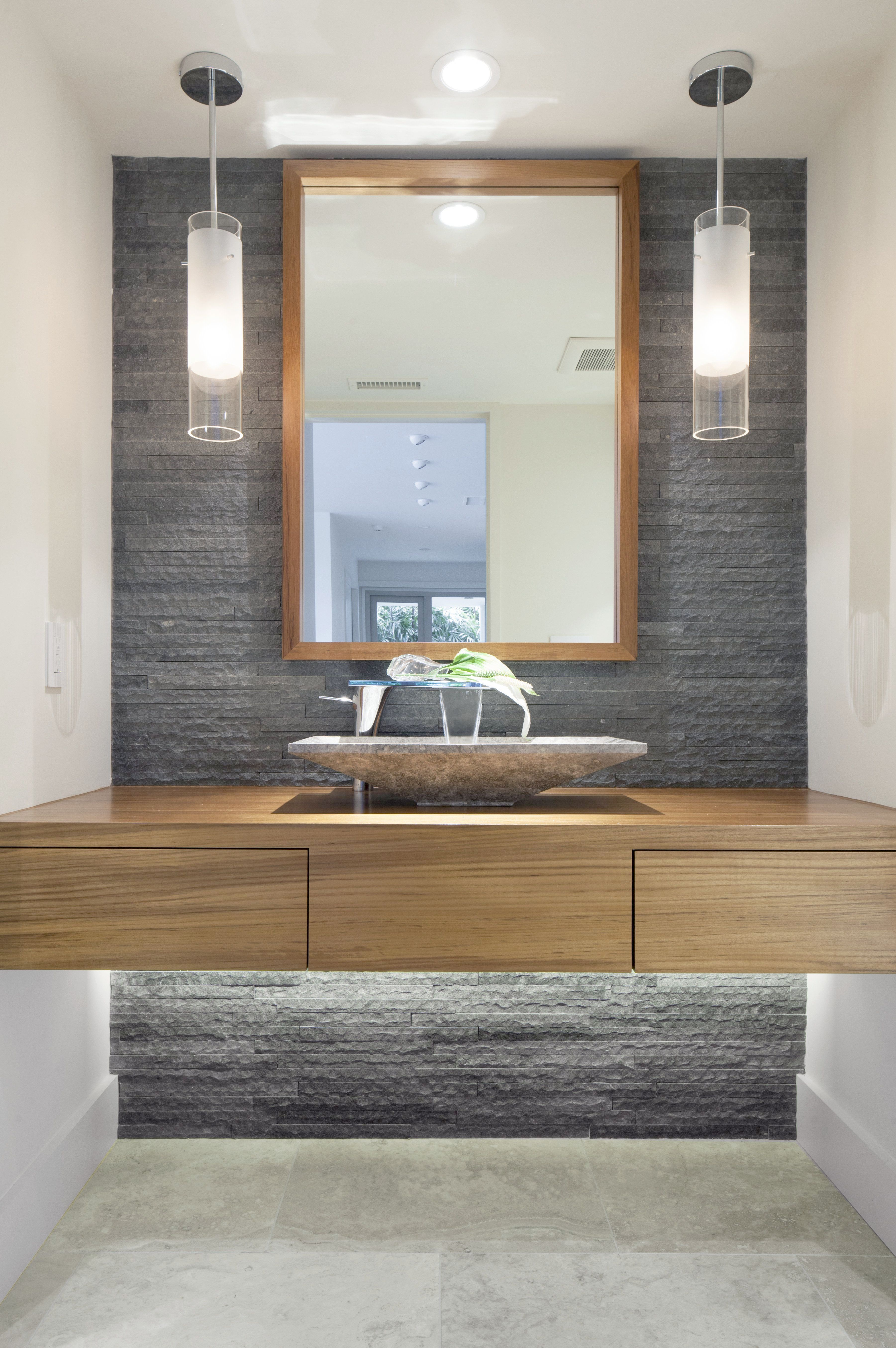 A Modern Bathroom With Natural Stone Accent Wall And Pendant