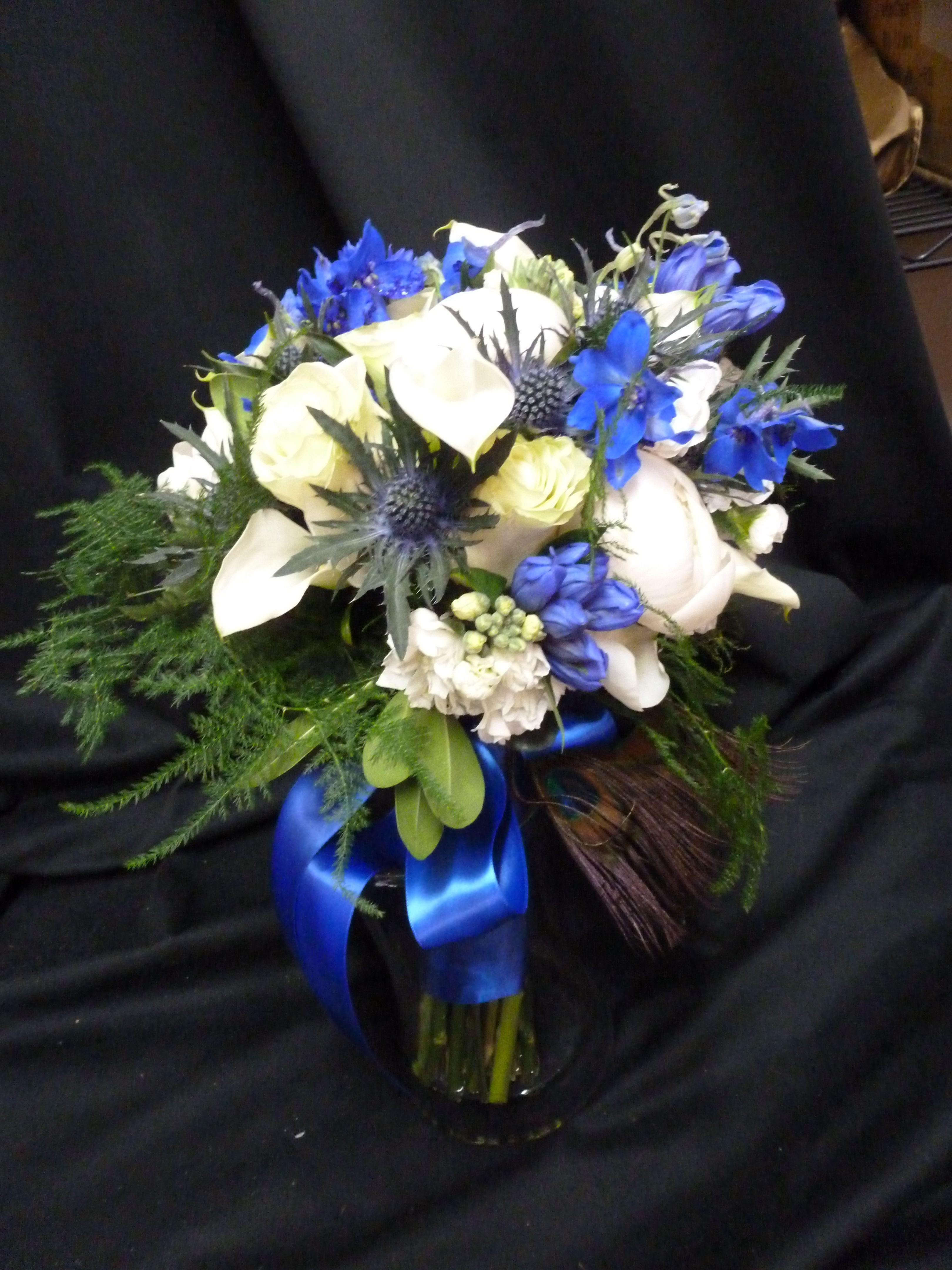An arrangement featuring blue delphinium white calla for Flower arrangements with delphinium