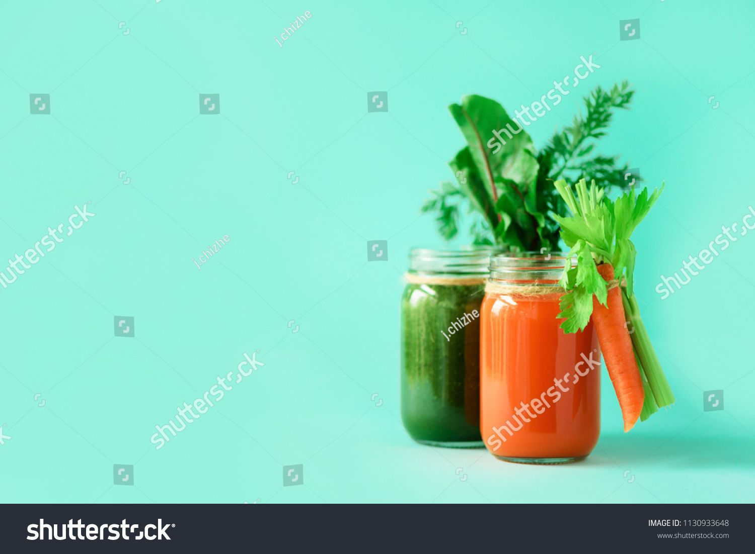 Two bottles of green and orange smoothies on blue background. Detox drinks in glass jar from vegetables - carrot, celery, beet greens and tops. Copy space. Summer food concept. , bottles of green and orange smoothies on blue background. Detox drinks in glass jar from vegetables - carrot, celery, beet greens and tops. Copy space. Summer food concept. ,