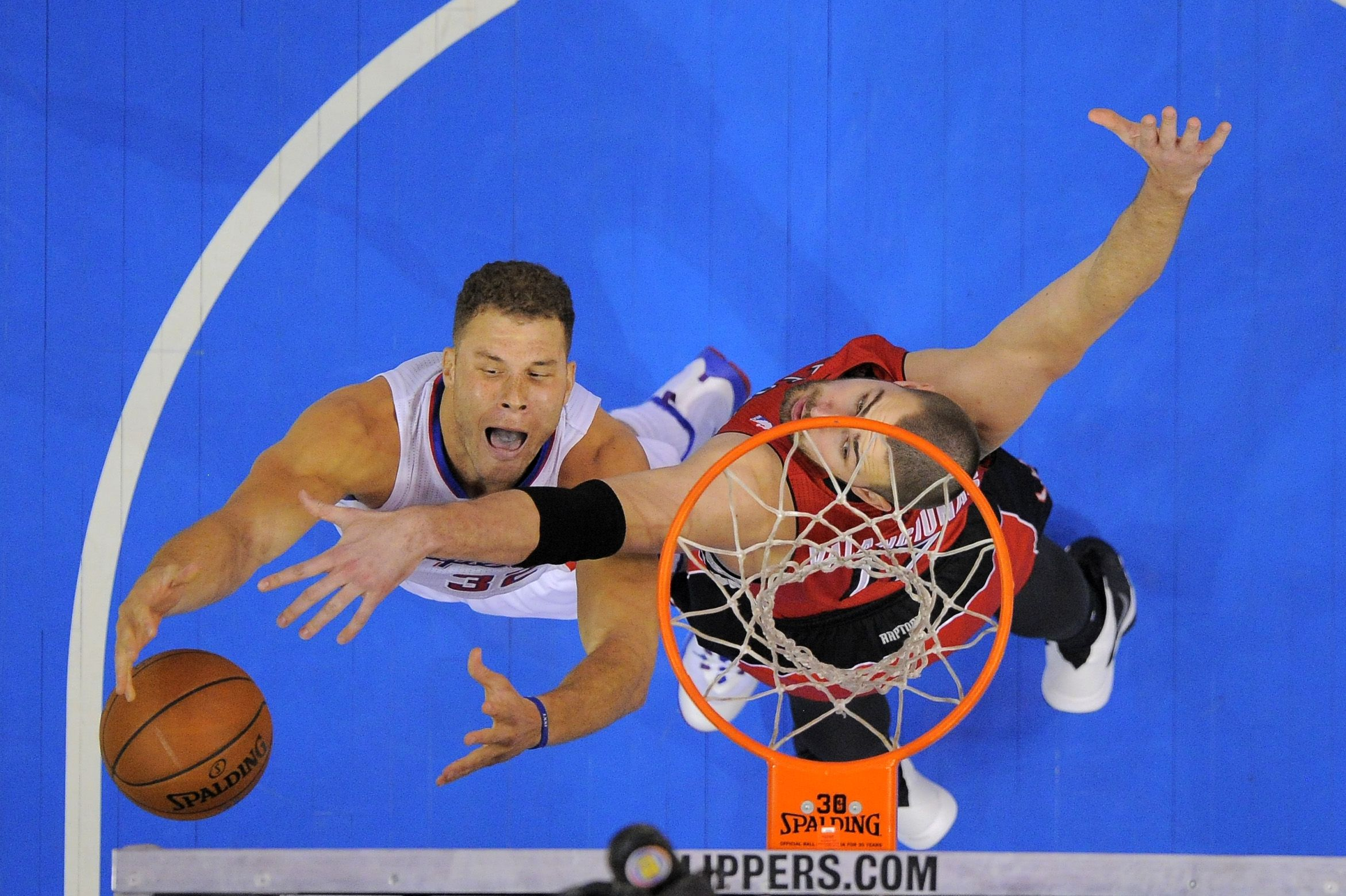 Los Angeles Clippers forward Blake Griffin, left, puts up a shot as Toronto Raptors center Jonas Valanciunas, of Lithuania, defends during the first half of an NBA basketball game, Friday, Feb. 7, 2014, in Los Angeles. (AP Photo/Mark J. Terrill)