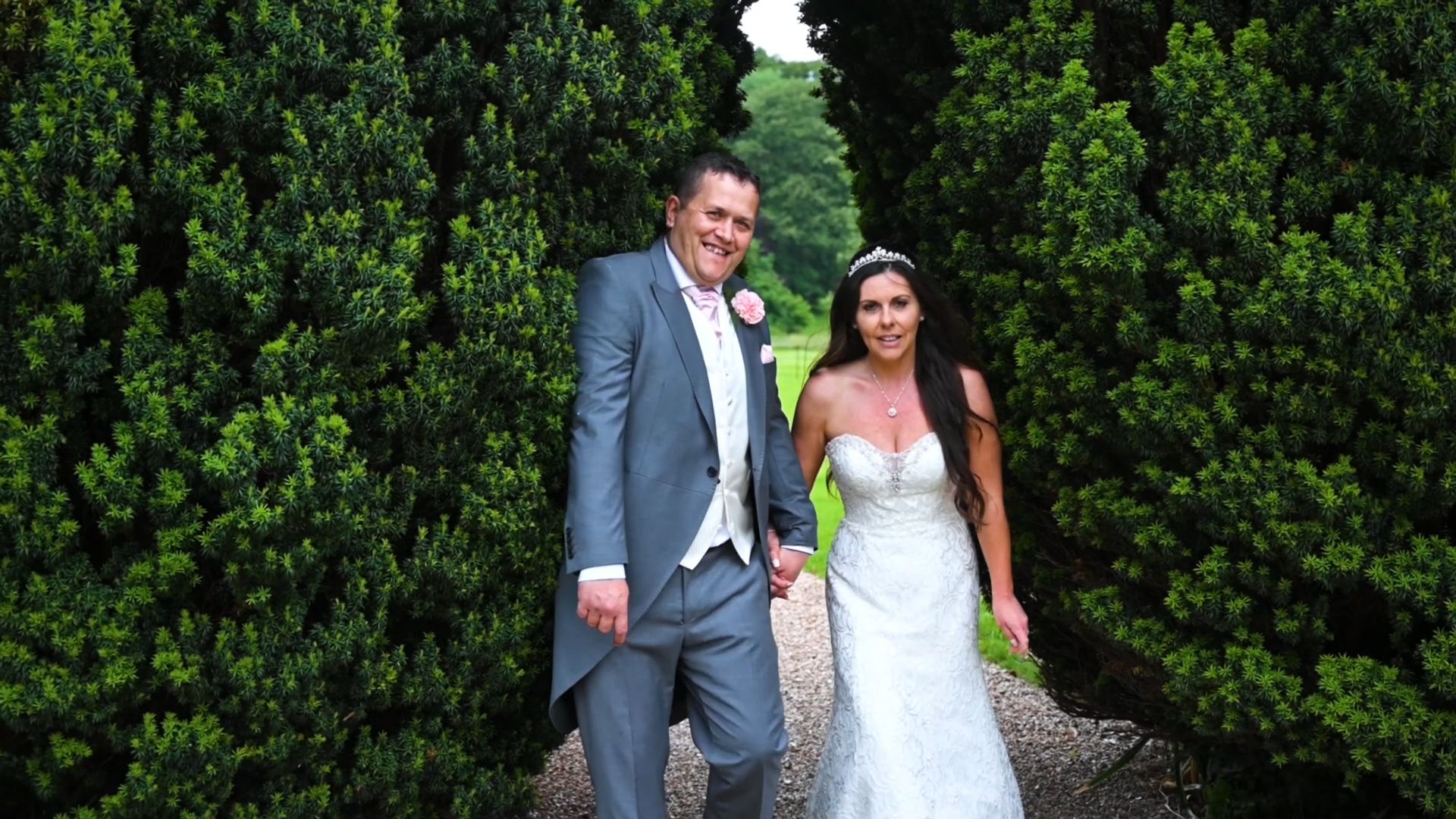 Bride and groom holding hands and walking the grounds of St Audries Park