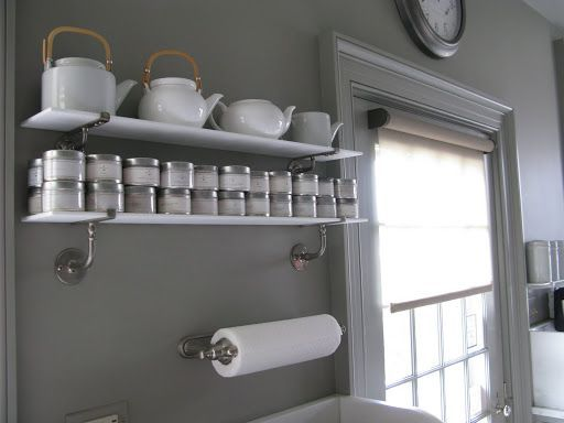 Over the kitchen sink are milk glass shelves that hold tea ...
