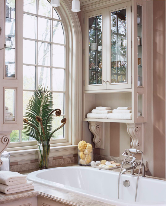Fabulous Bath Storage Ideas - Traditional Home® Tub-Side Convenience Intricate corbels and a hand-rubbed painted finish give this custom display cabinet (one of two) a sophisticated elegance. But it's the tub-side location that makes the cabinet a storage standout; the unit keeps towels and other bath products within easy reach of the bather.