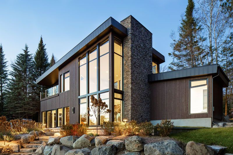 this modern lake house in canada has an exterior clad in wood stone and