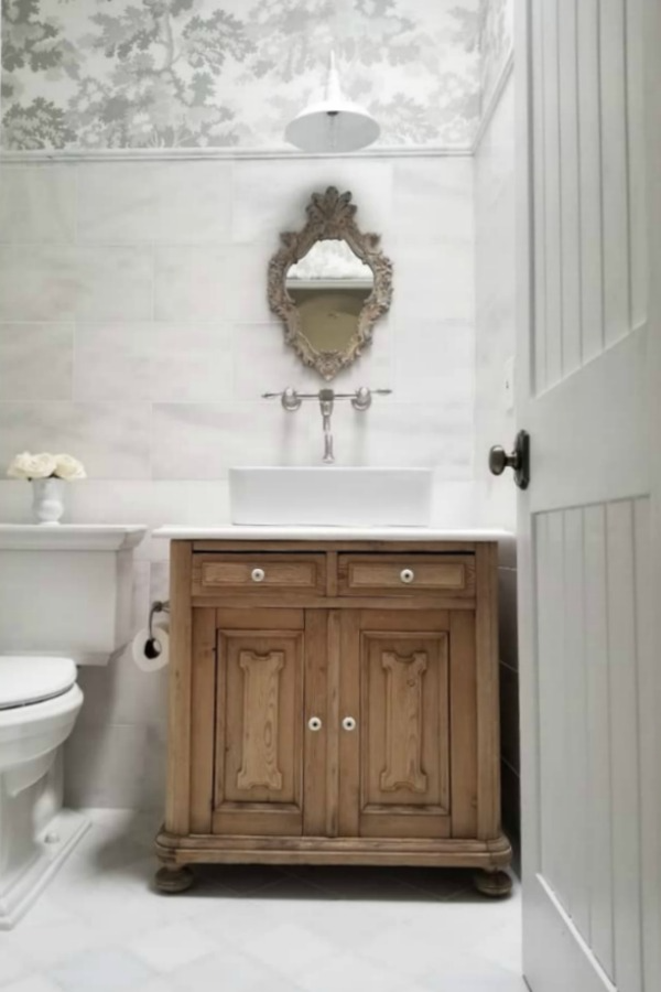 White French country bathroom with natural wood vanity and understated French country decor - The French Nest Co. #frenchcountry #interiordesign #whitebathroom #rusticelegance