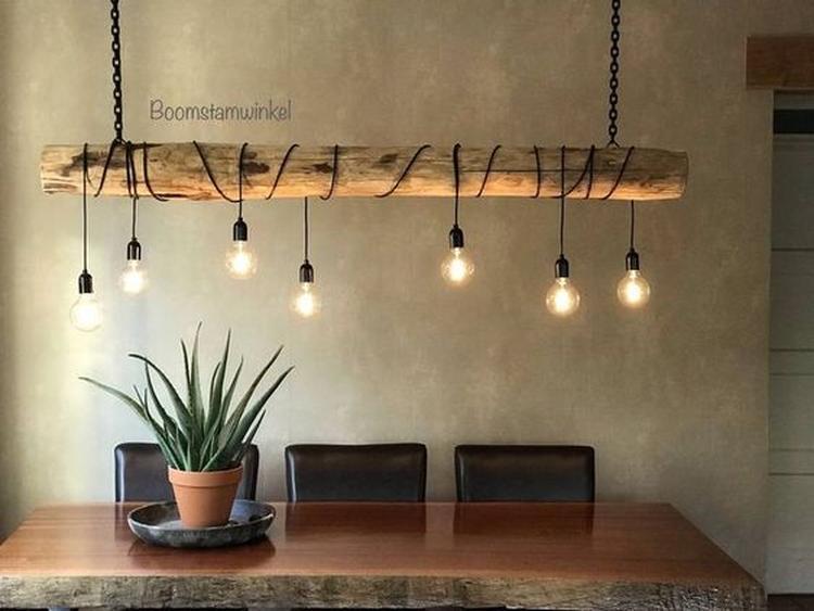Eine hausgemachte Lampe aus einem Baumstamm mit Lichtern um