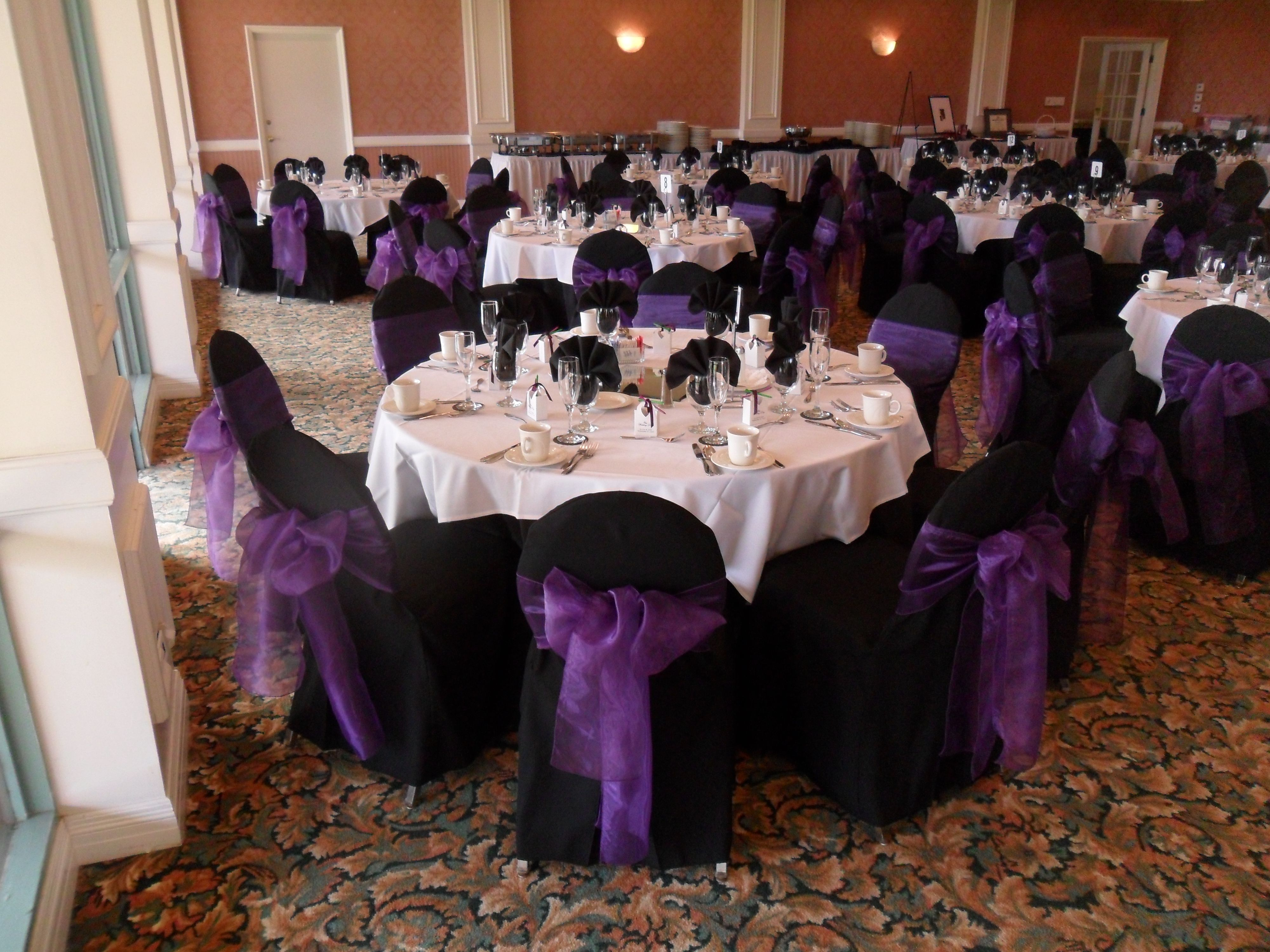 Regal Purple Bows On Black Chair Covers Available For Rent