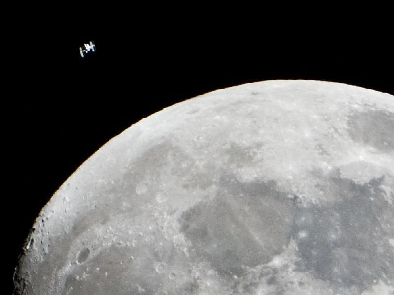 Space Station Flying by the Moon.  The International Space Station can be seen as a small object in upper left of this image of the moon in the early evening Jan. 4 in the skies over the Houston area flying at an altitude of 390.8 kilometers (242.8 miles). The space station can occasionally be seen in the night sky with the naked eye and a pair of field binoculars.