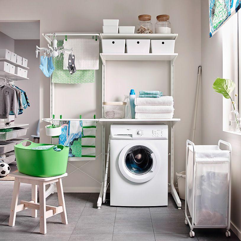 Vaskerom med oppbevaring bestående av tørkestativ og hyller fra gulv til tak. Vist sammen med en skittentøyskurv på hjul.