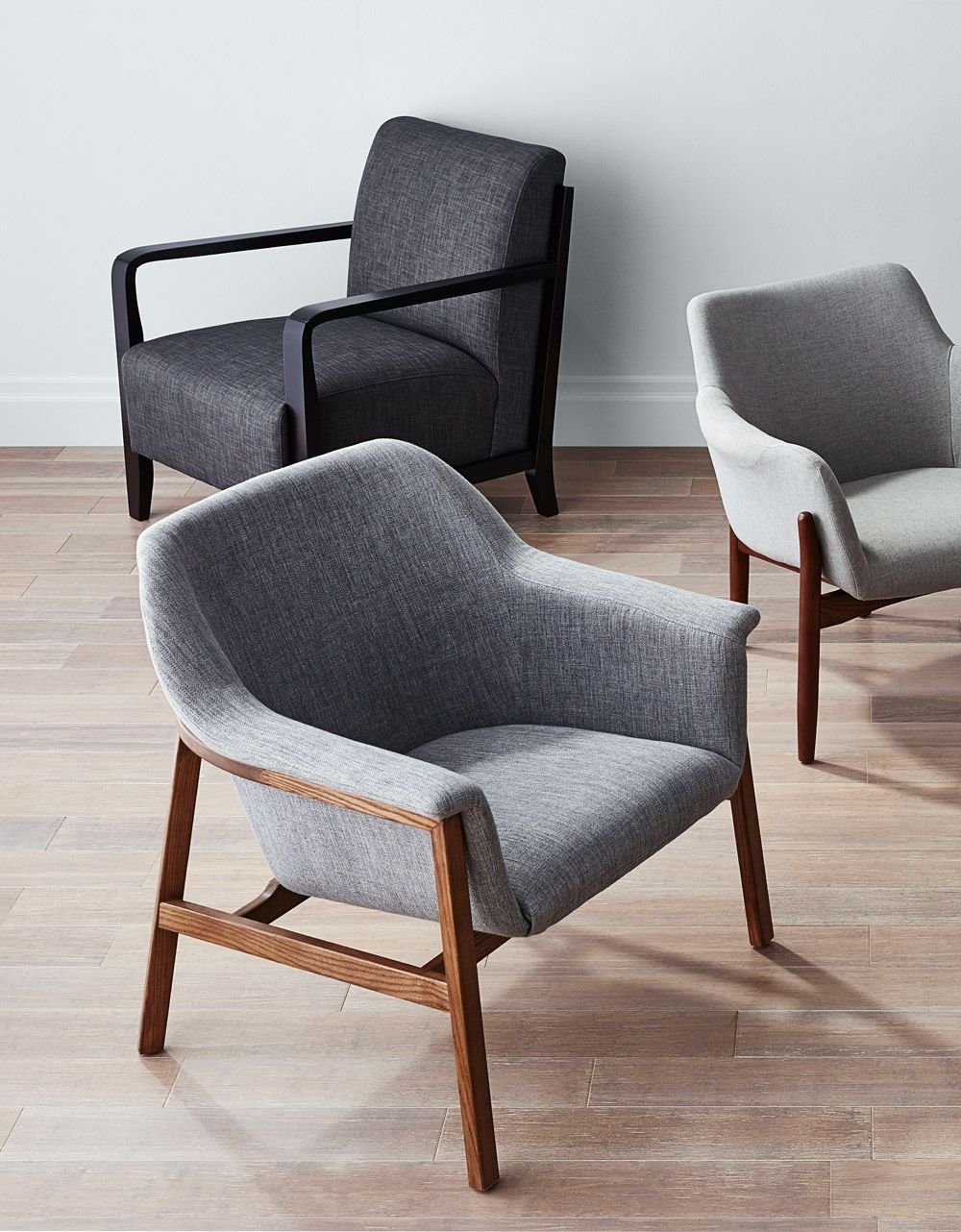 The charlie accent chair is made of solid american ash wood with a smoked walnut finish and is upholstered in grey textured cotton linen blend fabric