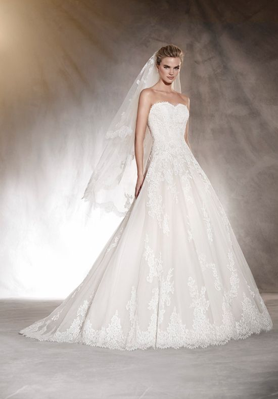 A classic and very elegant wedding dress. A princess cut dress with an off-the-shoulder neckline in lace and tulle with guipure and gemstone appliqués that blend into the waist creating a wonderful skirt in mikado that provides volume to this design. The Knot provides price estimates to give you a general idea of the cost of a dress. Please visit retailers in your area for exact pricing. Prices will vary by region.