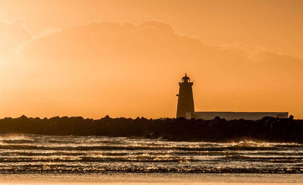 poolbeg lighthouse dublin ireland at sunrise by shotbymaguire