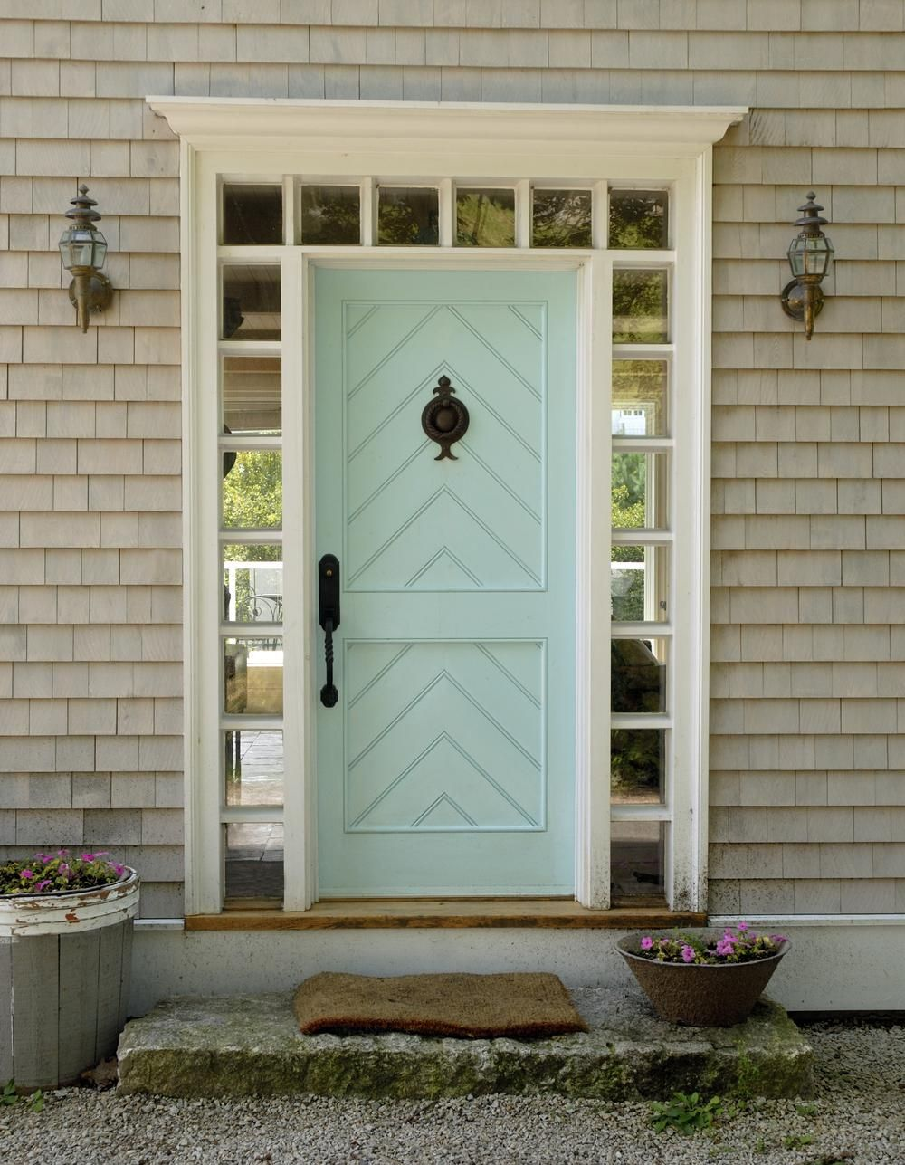 A front door can be a lovely way to pay homage to the home's locale. Here  an inlaid chevron panel detail, duck's-egg blue color, and ship-lantern  sconces ...