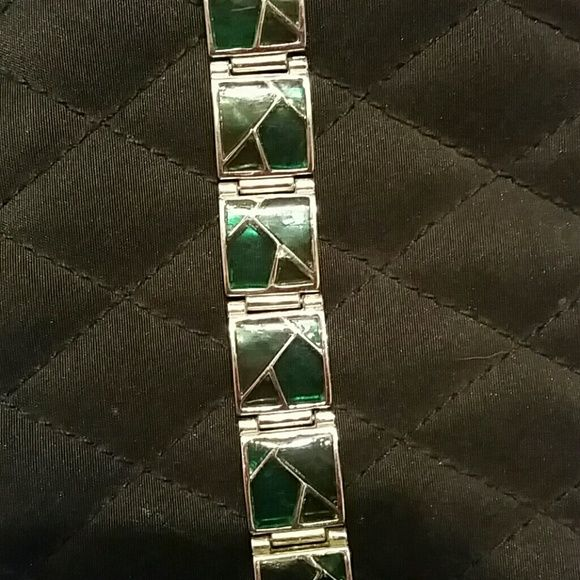 Bracelet with a stained glass look! This bracelet is beautiful, it's a few different shades of green depending on how the light hits it. Has the stained glass look. Silver accents seperatly each link along with silver clasp lock. Please see photo 4 to get a more accurate measurement. Jewelry Bracelets