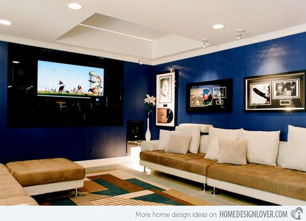 chic seating area with a brown sofa and a navy accent wall and ...