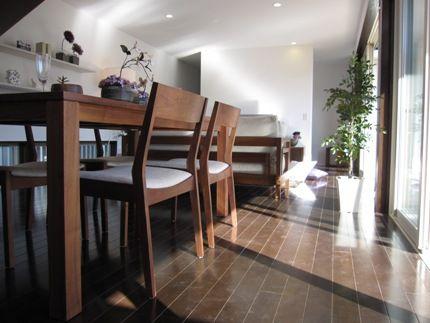 ダークブラウン色の床にウォールナット無垢の家具を合わせた