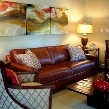 Transitional living room with Hickory Chair armchairs, leather sofa, modern coffee table, red accents, and original artwork (triptych) Designed by Pulliam Morris Interiors