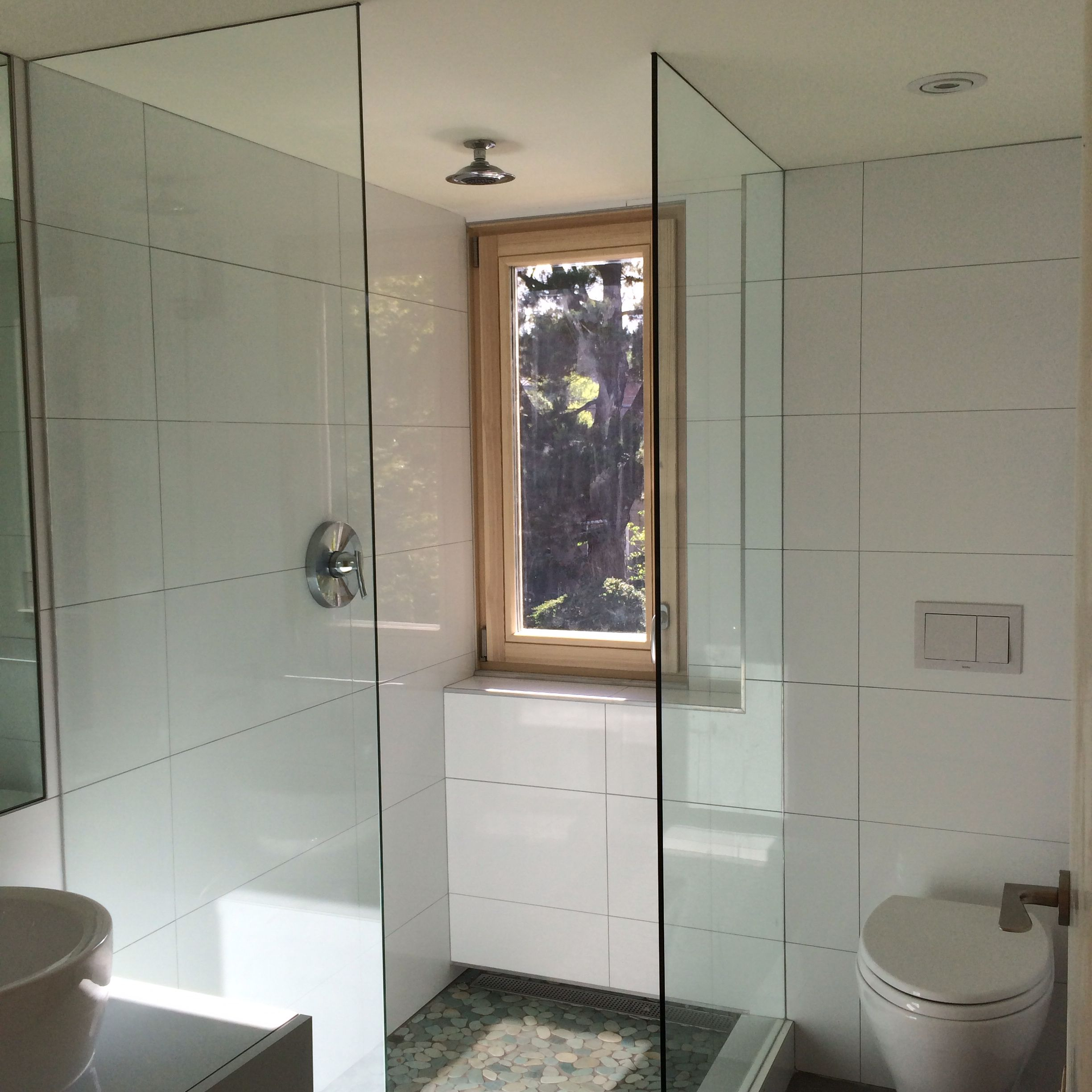Oversized High Gloss White Tile Bathroom Walls With Washed Green Pebble Floors And Recessed Tem White Tile Bathroom Walls White Wash Walls White Bathroom Tiles