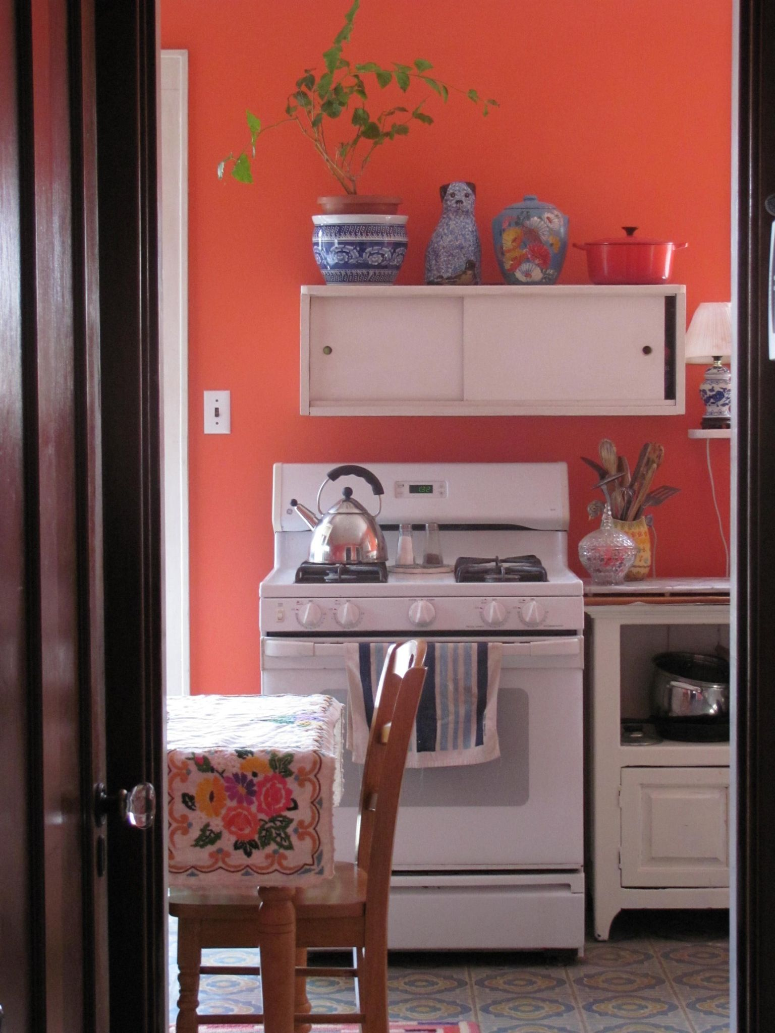 Coral kitchen walls with white cabinets orange kitchen walls coral - Sherwin Williams Daring My Kitchen Walls Won T Be This Saturated But There S A Good Feeling In This Room With The White Stove And Printed Tablecloth
