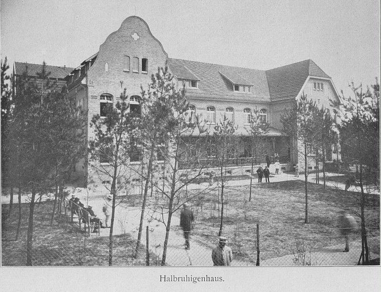 Schwarz-Weiß-Foto: dreistöckiges Haus mit einem Zaun rundherum und Bäumen im Vordergrund