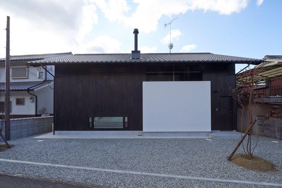 モダン和風 ・和瓦に薪ストーブの煙突が良く似合う。(明日香の家)奈良県橿原市・木の家・秦建築