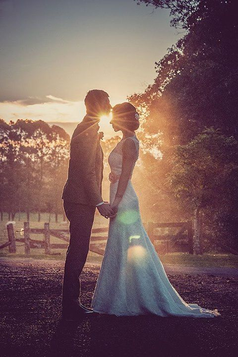 The bride and groom share a sweet moment together at sunset, basked in the natural glow