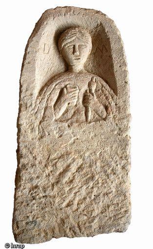 Stèle funéraire gallo-romaine en arkose (hauteur 103 cm, largeur 50 cm), première moitié du IIe s. de notre ère, nécropole de Pont-l'Évêque Autun Personnage féminin en buste: la main droite tient un gobelet, la main gauche une quenouille et son fuseau, instruments nécessaires au travail de la laine. Des lettres D et M apparaissent de part et d'autre du personnage (iDiis Manibus, aux dieux Mânes)...