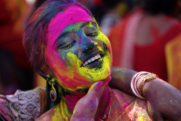 Indian women apply colored powder on each other as they celebrate the Holi festival in India, March 16, 2014.