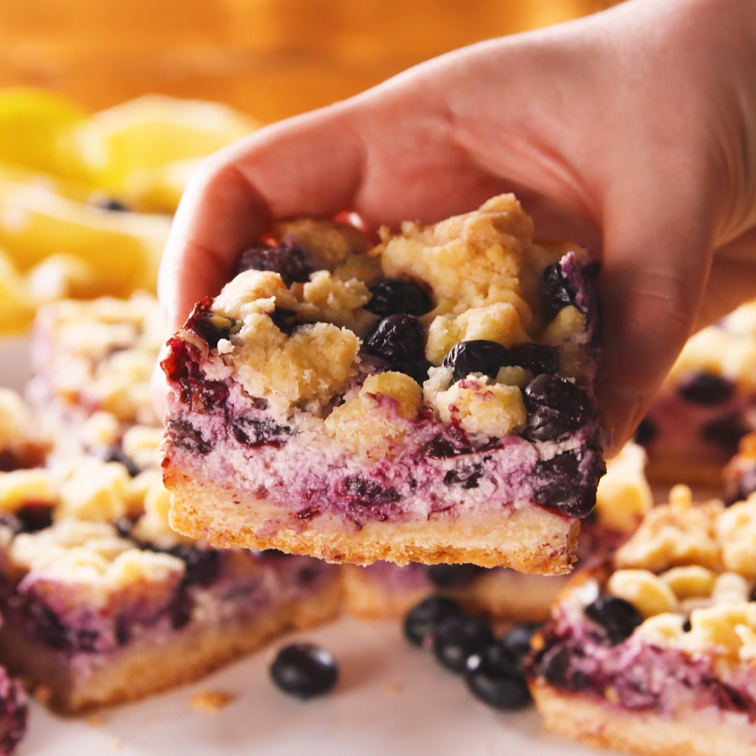 Lemons and blueberries go together like spring and sunshine. They are the perfect combo and these bars are our favorite yet! This 5-star lemon blueberry pound cake still has a place in our hearts though. Get the recipe at .