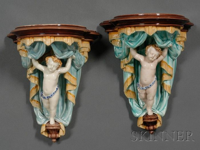 Two Wedgwood Majolica Wall Brackets, England, c. 1875, each polychrome decorated and molded with a single putti beneath a braided curtain.