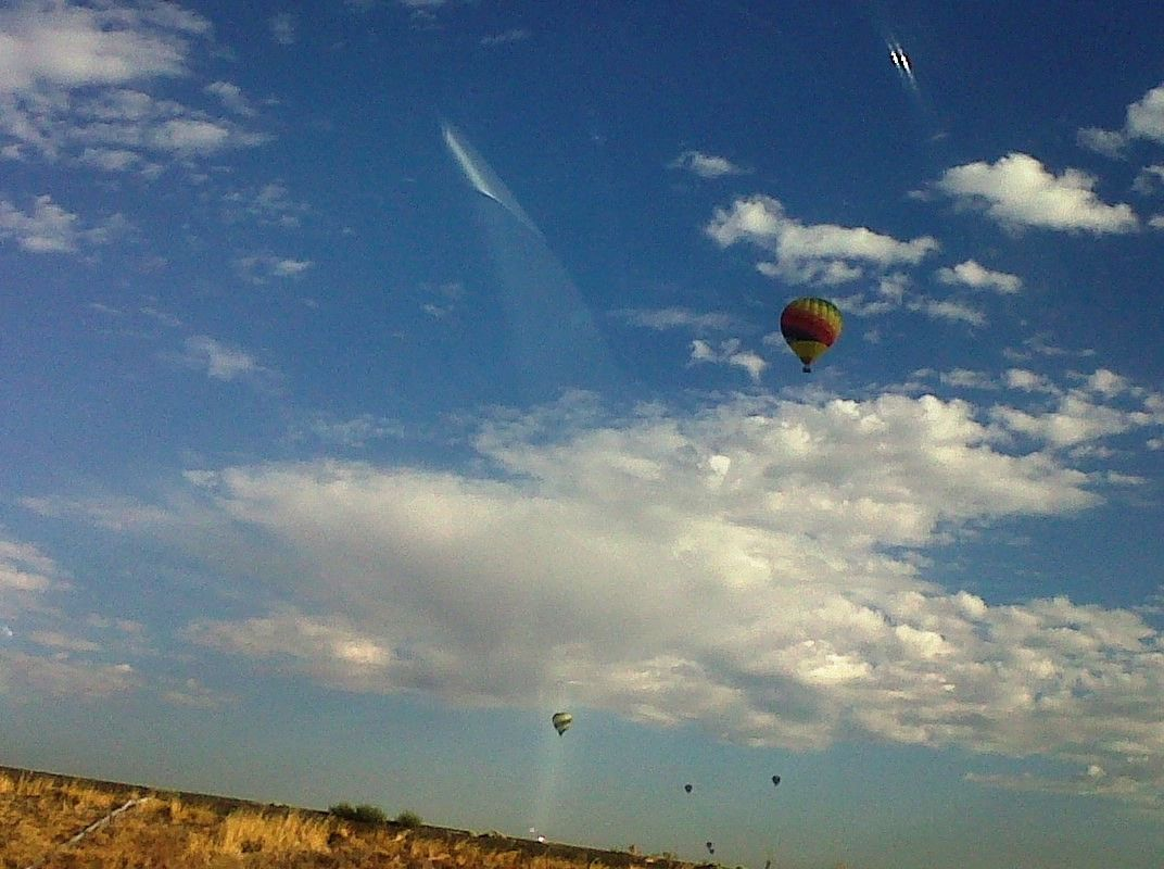 Beautiful clouds sharing the sky with hot air ballons