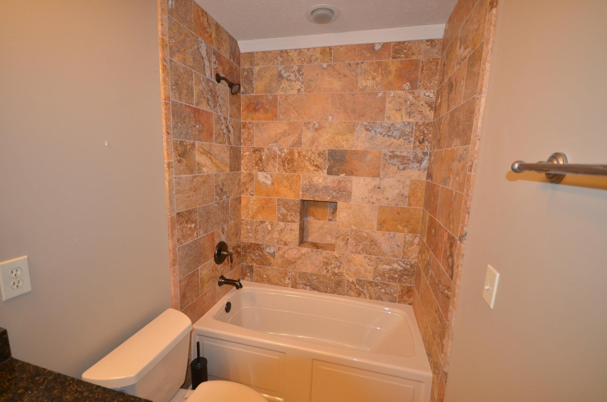 Example of large subway tiles in bathtub surround with niche ...