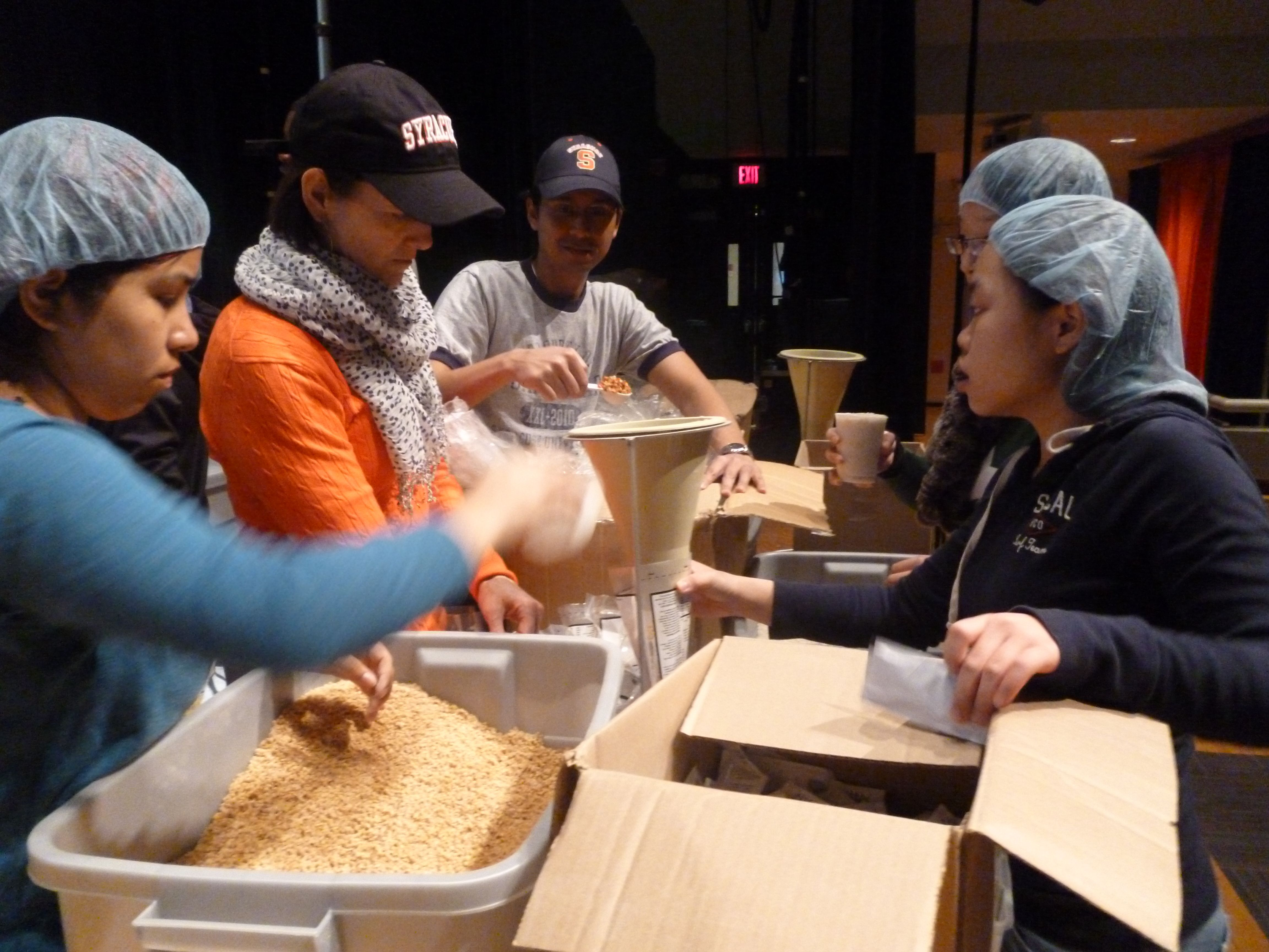 Students and staff working together at the Stop Hunger Now food packaging event.