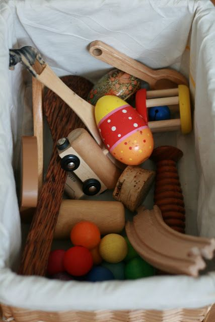 Wood/ natural basket: Various size and shape wooden spoons and implements A beautiful, painted wooden egg A wooden train A large piece of cork A wooden bell Various other wooden toys or wooden implements It would also be lovely to include some driftwood and some pine cones in this basket.