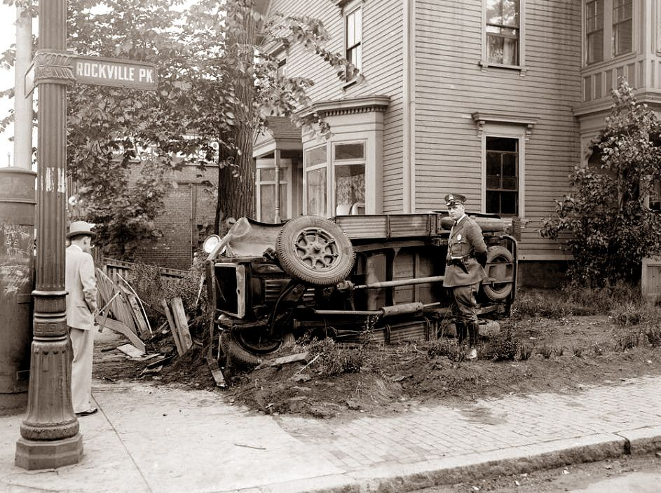 A police officer poses next to a car that flipped over manoevring around corner in Roxbury, Massachusetts in 1935.