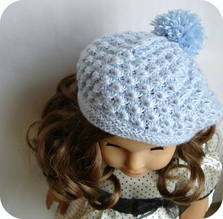 """Rosamund is a sweetly feminine beret done in a highly textured stitch pattern that resembles little flowers, and is topped with a plump pom pom. It's designed to fit 18"""" dolls with a head circumference of approximately 12 ¼"""", like American Girl. It's worked in the round on double pointed needles, and requires minimal finishing. It would go with jeans and a casual top just as well it is does with a dress."""