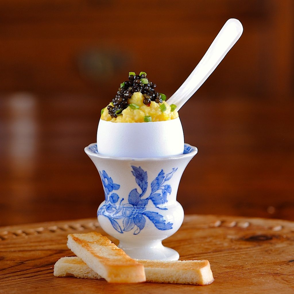 Creamy scrambled eggs topped with caviar served in an egg