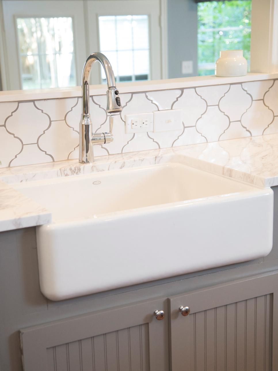 Fixer upper marble kitchen - A Moroccan Tile Backsplash Carrara Marble Countertops And A Farmhouse Sink Add Charming Character To