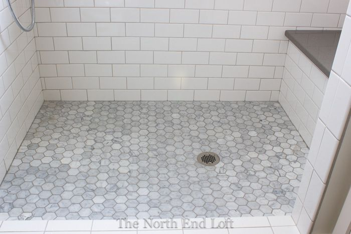 The shower floor is hexagon shaped marble tiles with darker gray grout we had the marble sealed Marble hex tile bathroom floor